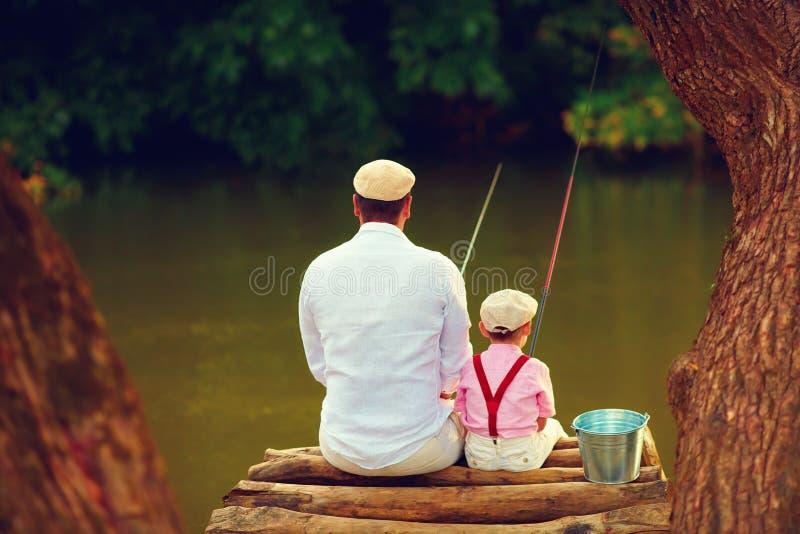 Leuke vader en zoon die samen onder mooie oorspronkelijke aard vissen royalty-vrije stock foto