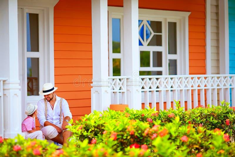 Leuke vader en zoonszitting en het spreken op portiek, Caraïbische straat royalty-vrije stock afbeelding