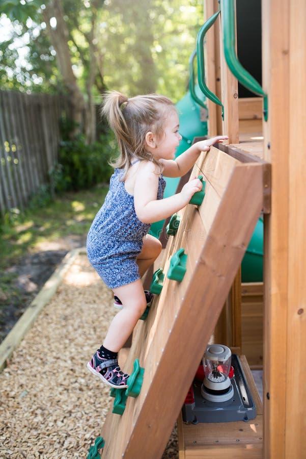 Leuke 2 - 3 van het oude peuterjaar kind die pret hebben die op kunstmatige keien proberen te beklimmen stock foto's