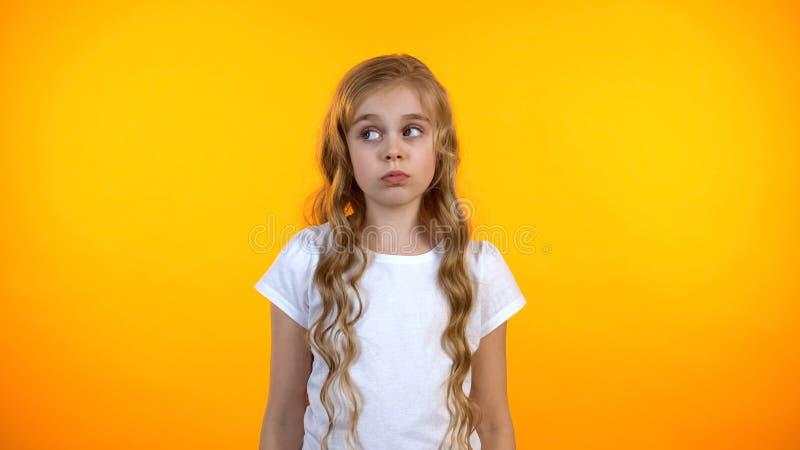Leuke verward preteen meisje het kijken opzij voelend onzeker gebrek aan ideeën, keus royalty-vrije stock afbeelding