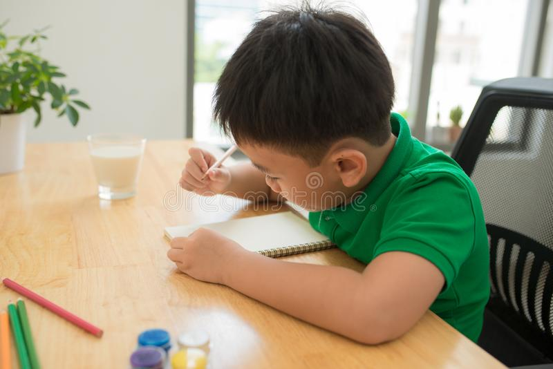 Leuke verwarde glimlachende jongen die thuiswerk doen, kleurend pagina's, writin royalty-vrije stock afbeeldingen
