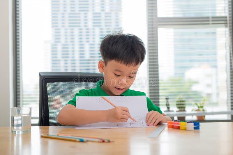 Leuke verwarde glimlachende jongen die thuiswerk, het kleuren van pagina's, het schrijven en het schilderen doen De kinderen schi stock fotografie