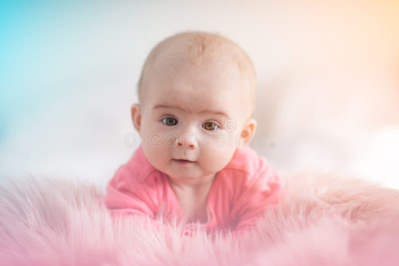 Leuke vijf maanden oud van het Babymeisje de zuigelings op een bed op haar buik met hoofd die omhoog naar camera met haar grote o stock foto
