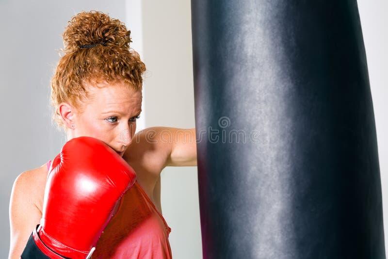 Leuke volwassen bokser die ponsenzak met behulp van stock foto
