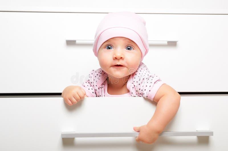 Leuke vrolijke baby, die in een ladeborst zitten royalty-vrije stock foto
