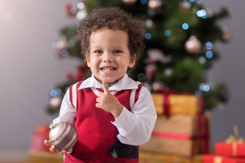 Leuke vrolijke jongen die een Kerstboomdecoratie houden stock foto