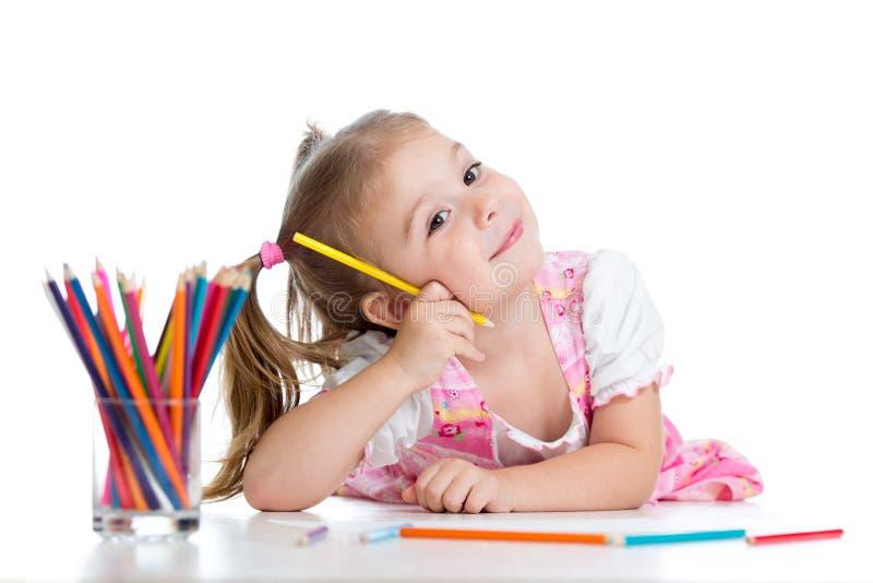 Leuke vrolijke kindtekening die potloden gebruiken terwijl het liggen op vloer royalty-vrije stock afbeelding