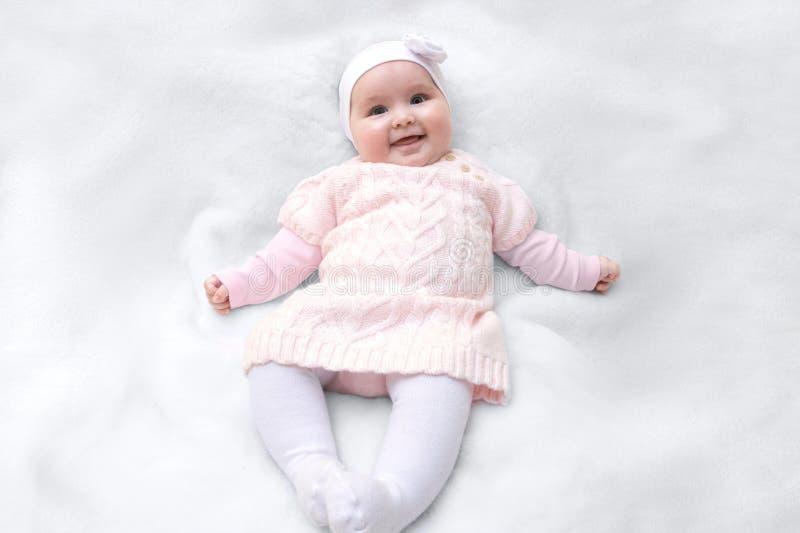 Leuke vrolijke pasgeboren gekleed in roze overhemdskleding op witte bontdeken Aanbiddelijke zuigelingsbaby met hoofdband stock foto's