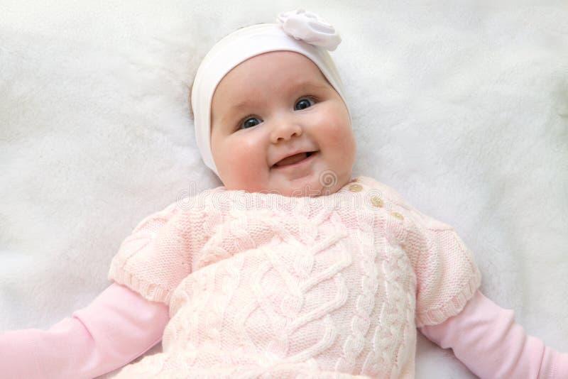 Leuke vrolijke pasgeboren gekleed in roze sweater op witte bontdeken Aanbiddelijke zuigelingsbaby met hoofdband royalty-vrije stock foto's