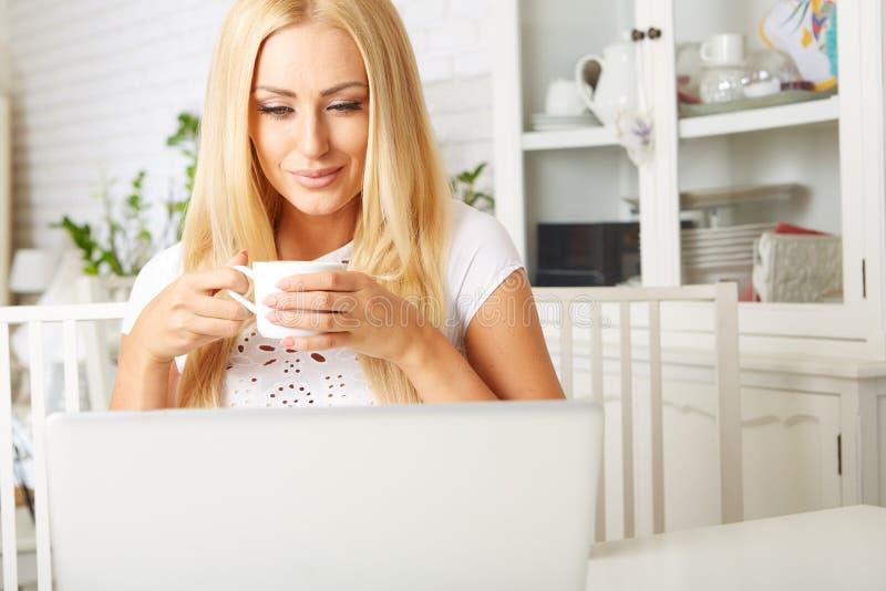 Leuke vrouw die een kop thee hebben terwijl het gebruiken van haar royalty-vrije stock afbeelding