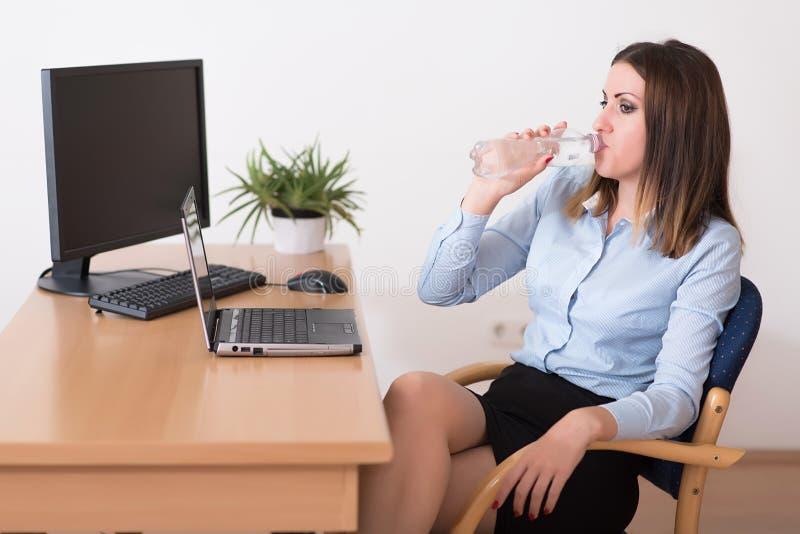 Leuke vrouw die een water in het bureau drinkt stock afbeeldingen