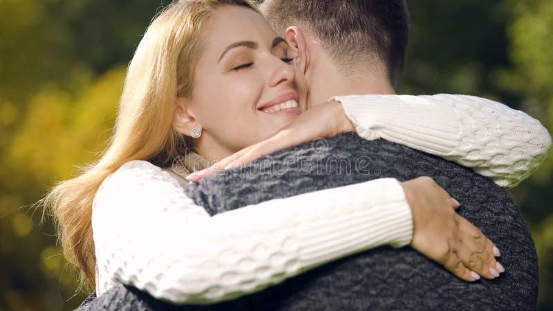 Leuke vrouw die teder echtgenoot, romantische datum omhelzen die in openlucht, liefde voelen royalty-vrije stock afbeelding