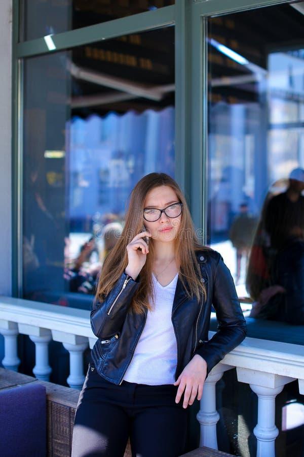 Download Leuke Vrouw In Glazen Die Op Smartphone Bij Straatkoffie Spreken Stock Afbeelding - Afbeelding bestaande uit glazen, overhemd: 114227605