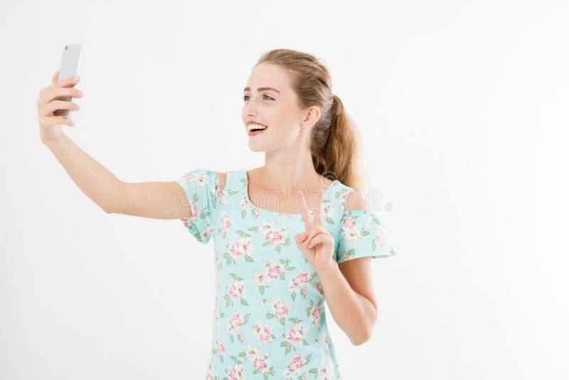 Leuke vrouw in kleding die een selfie nemen die en het teken van overwinning of vrede tonen, op witte achtergrond, exemplaarruimt stock foto's