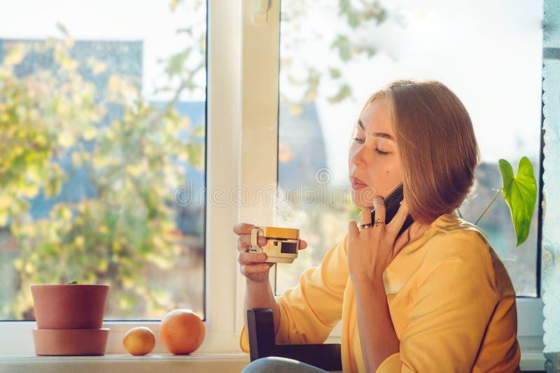 Leuke vrouw met een mol op haar wang die op de telefoonzitting dichtbij het venster met een mok thee spreken stock fotografie