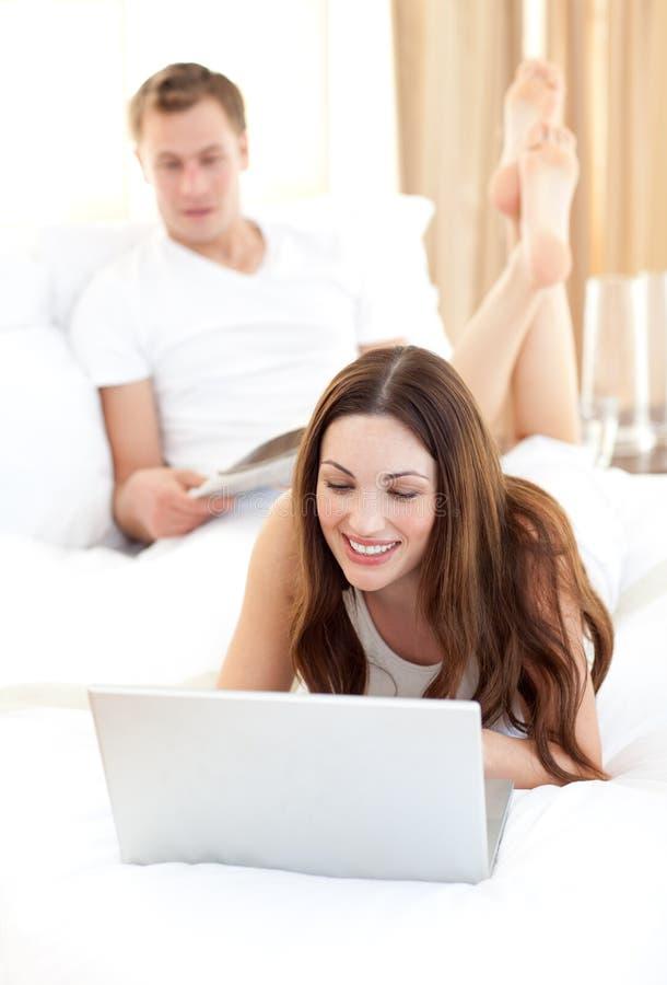 Leuke vrouw met haar echtgenoot die bij laptop werkt royalty-vrije stock foto