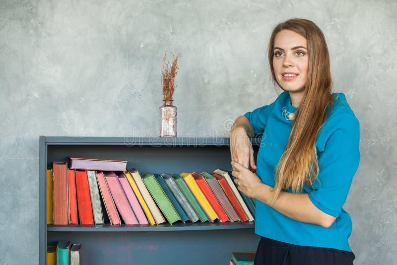 Leuke Vrouw op Boekenrekkenachtergrond stock foto's