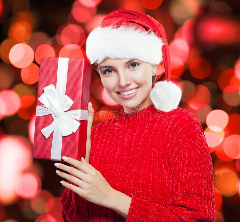 Leuke vrouw in Santa Claus-hoed met gift op rode bokehachtergrond royalty-vrije stock afbeelding