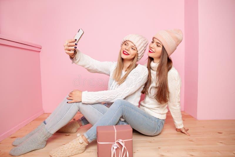 Leuke vrouw twee die met rode lippen en hoeden gift onderling delen Het maken selfie door smartphone Conceptenkerstmis royalty-vrije stock foto's