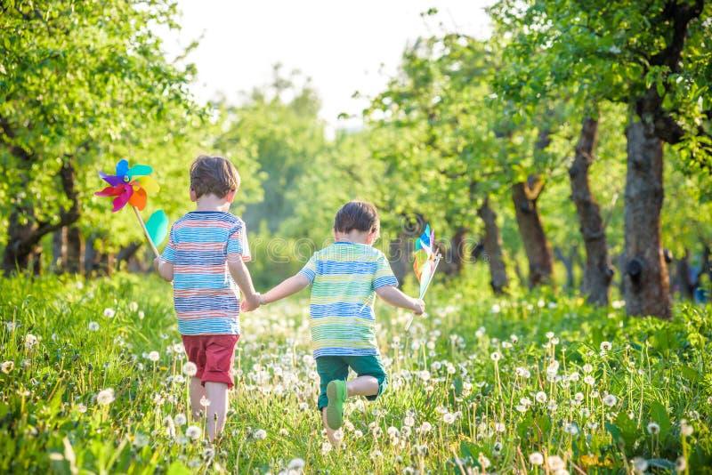 Leuke weinig jongen het water geven installaties met gieter in de tuin Activiteiten met kinderen in openlucht royalty-vrije stock afbeelding