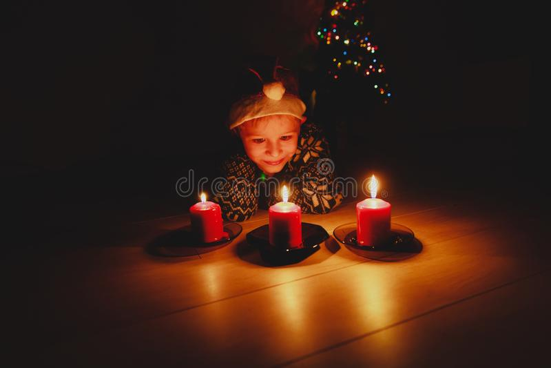 Leuke weinig jongens blazende kaarsen die bij wens bij Kerstmis maken stock fotografie