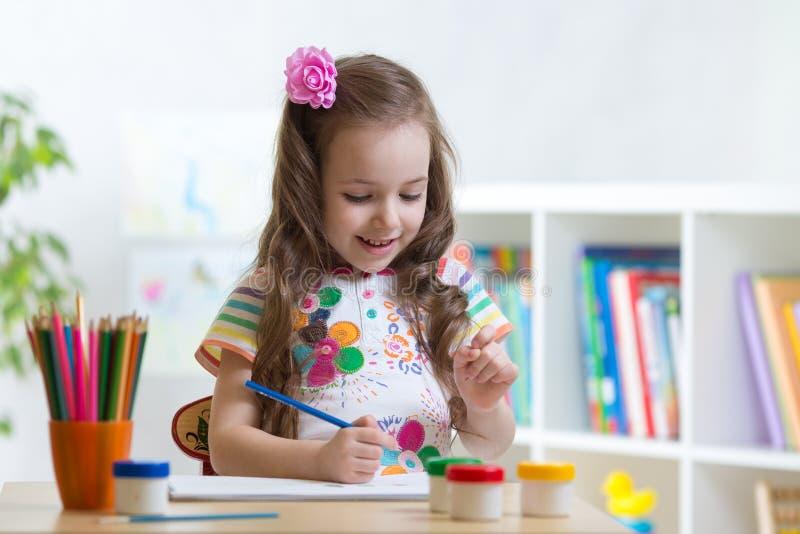 Leuke weinig van de het meisjestekening van het kleuterkind kleurenpotloden thuis of studio stock fotografie