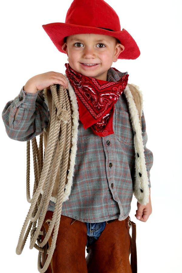 Leuke zeer jonge cowboy die kabel het glimlachen houden stock foto's