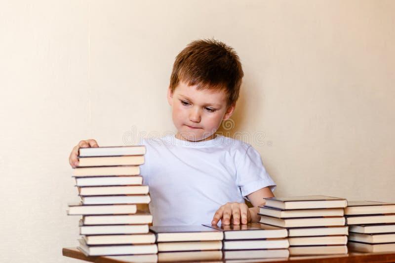 Leuke zes-jaar-oude jongen en vele boeken Leer te lezen royalty-vrije stock foto