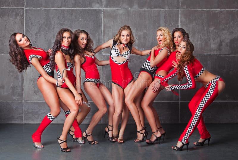 Leuke zeven gaan-gaan sexy meisjes in rood het rennen kostuum stock fotografie