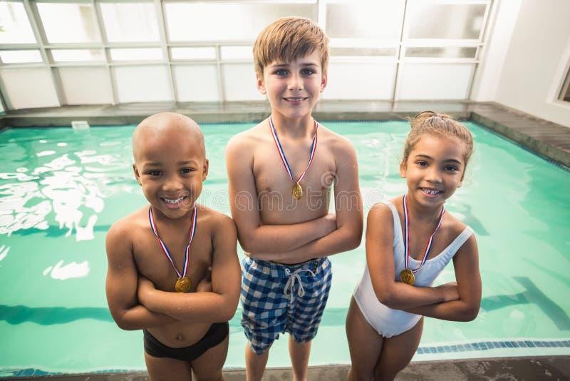 Leuke zwemmende klasse die met medailles glimlacht stock foto