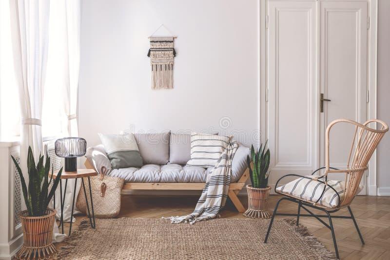 Leunstoel dichtbij beige bank met hoofdkussens in woonkamerbinnenland met installaties en deur Echte foto stock fotografie