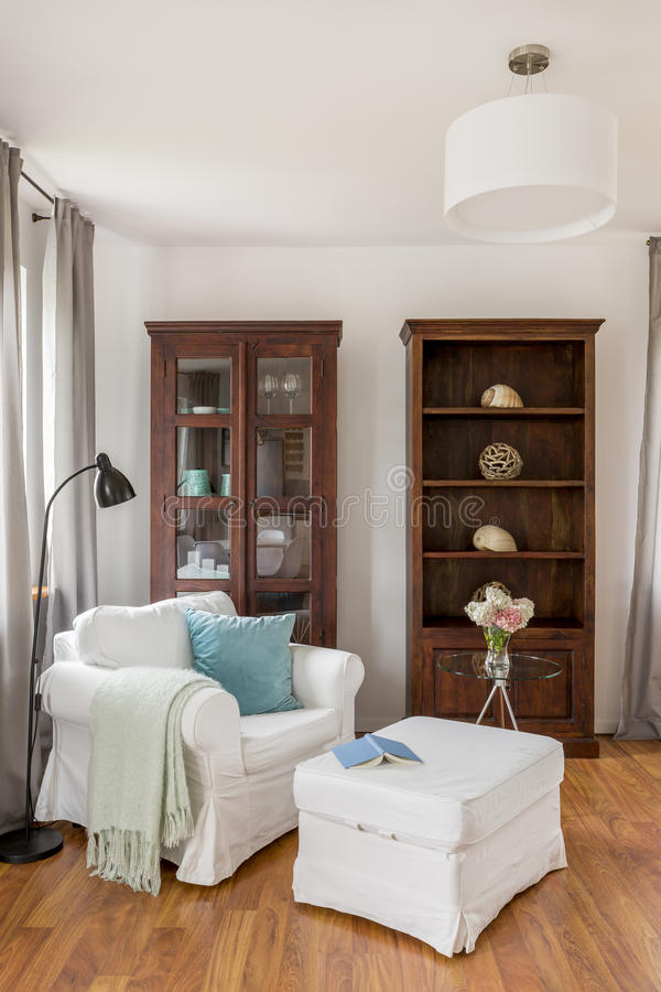 Leunstoel met poef en modieuze houten vitrines royalty-vrije stock afbeeldingen