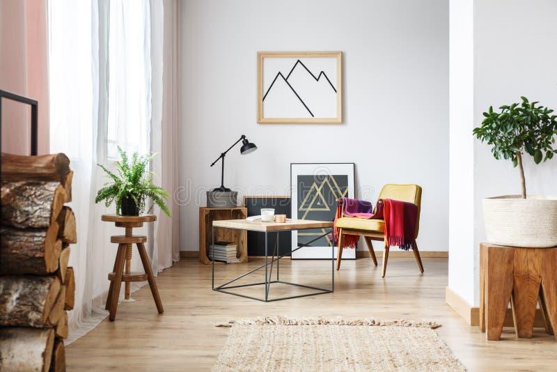 Leunstoel, minimalistisch affiche en brandhout stock foto