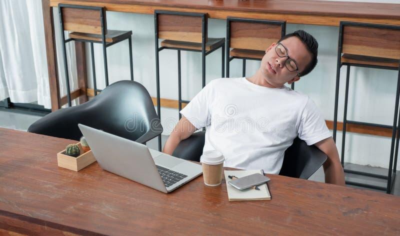 Leunt de toevallige mens van Azië dat gevoel achterover van het werk bij laptop in coffe wordt vermoeid royalty-vrije stock afbeeldingen