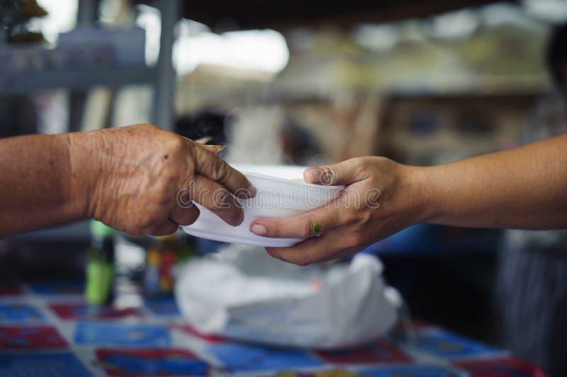 Leute übertreffen, um Nahrung von den Freiwilligen zu spenden: Nahrungsmittelkonzept der Hoffnung: Freie Nahrung für Armen und Ob lizenzfreies stockfoto