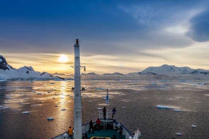 Leute auf dem ship& x27; s-Plattform, welche die Sonnenuntergangansicht unter Eisberg aufpasst lizenzfreie stockfotos