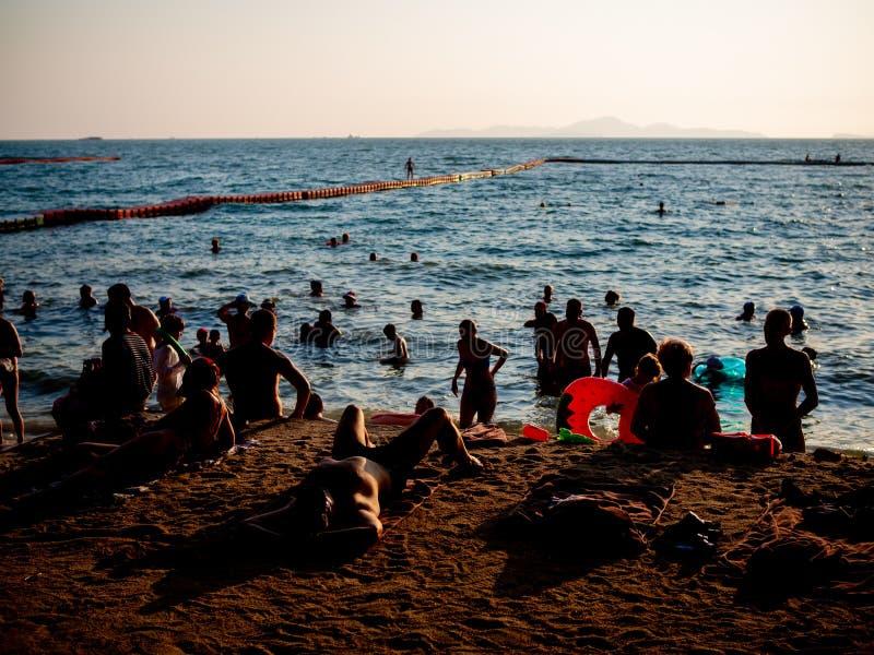 Leute auf dem Strand auf Sonnenuntergang stockfoto