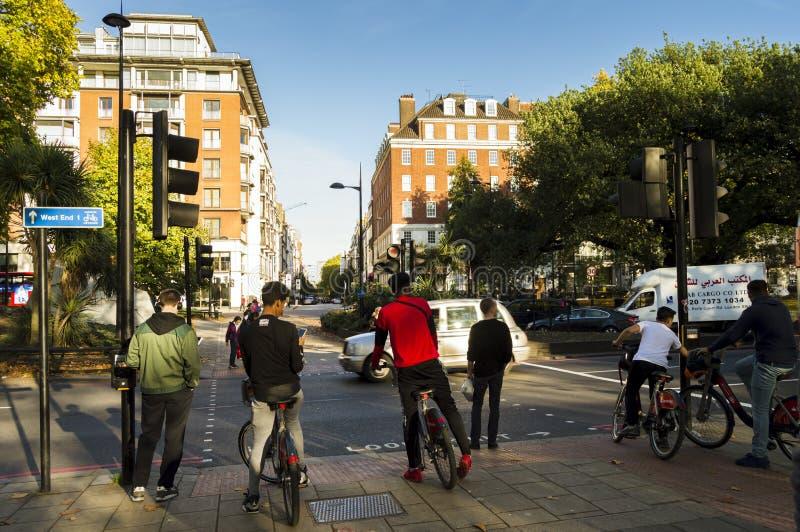 Leute auf den Fahrrädern, die an der Ampel nahe Hyde Park warten lizenzfreie stockfotos