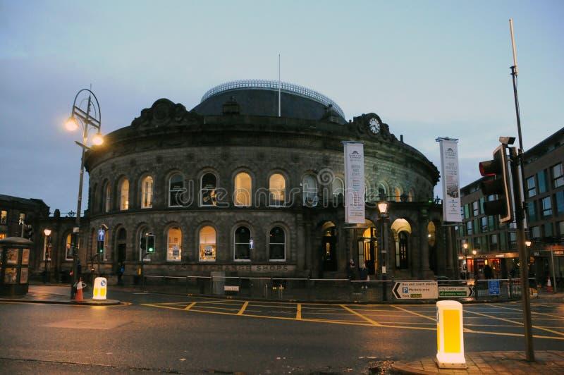 Leute auf den Schritten des historischen Getreidebörsegebäudes im Leeds-Stadtzentrum nachts mit belichteten Fenstern und Straßenl lizenzfreie stockbilder