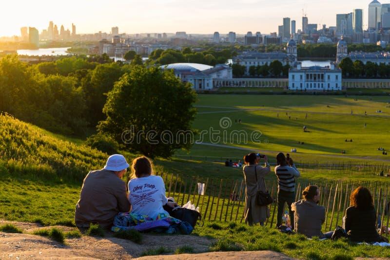 Leute auf die Oberseite des Hügels in Greenwich parken, passen den Sonnenuntergang auf und machen Fotos stockbild
