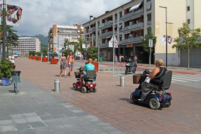 Leute auf elektrischen Rollstühlen reiten hinunter die Straße in Calella lizenzfreie stockfotos