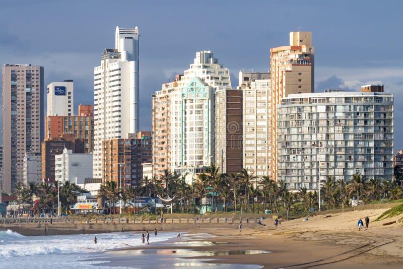 Leute auf früher Morgen-Strand gegen Stadt-Skyline lizenzfreie stockfotografie