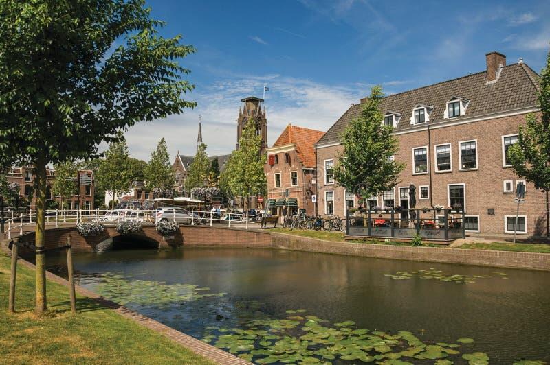 Leute auf Kanal von Bäumen gesäumt, Backsteinhäusern und Brücke mit sonnigem blauem Himmel in Weesp stockfoto