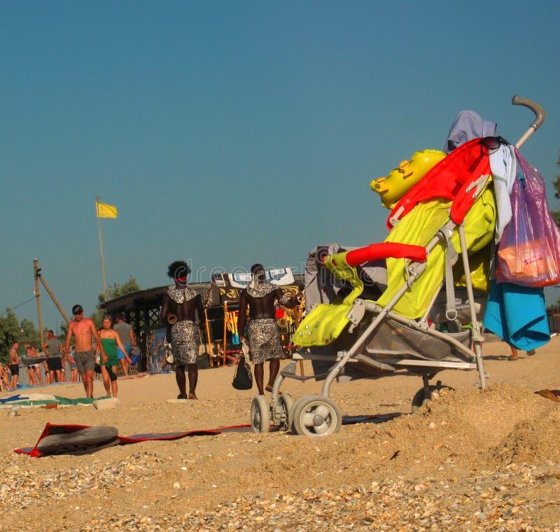 Leute auf sandigem Meer setzen im Sommer auf den Strand, verwanzt im Vordergrund lizenzfreie stockfotografie