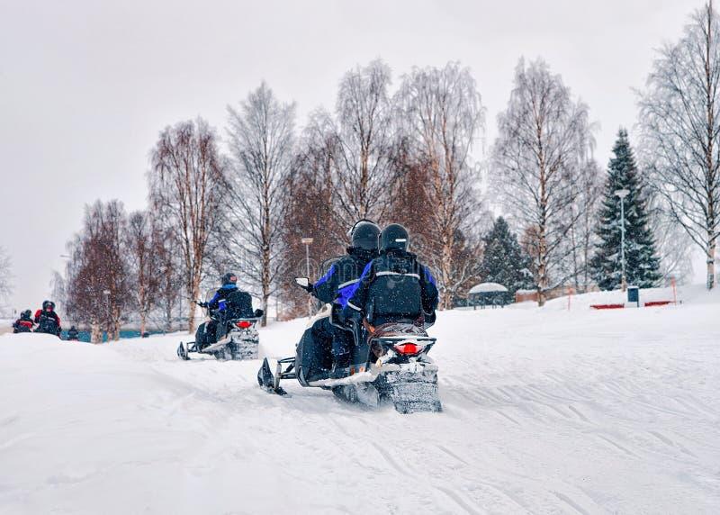 Leute auf Schneemobiles Winter Finnland Lappland während des Weihnachten stockfotos