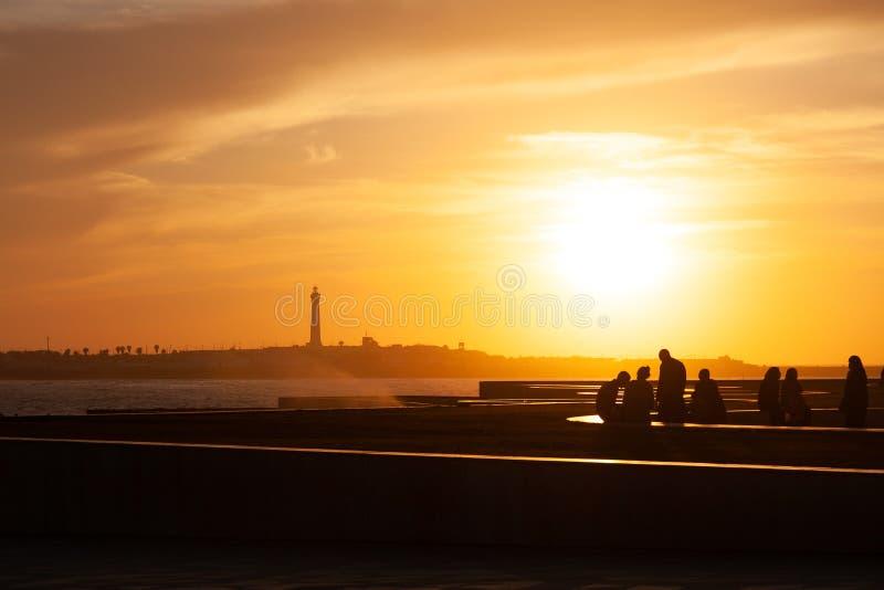 Leute auf Seeküste in Marokko bei Sonnenuntergang lizenzfreies stockbild