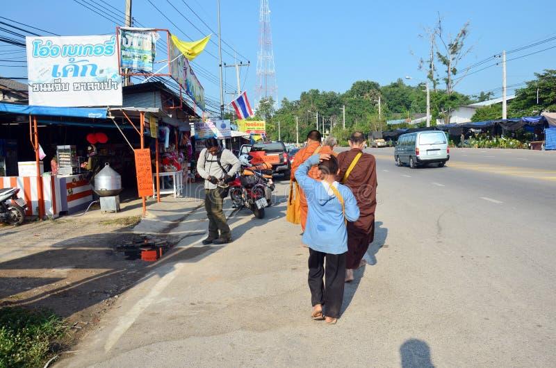 Leute beten mit Mönch und setzen Lebensmittelangebote zur buddhistischen Almosenschüssel lizenzfreie stockfotos