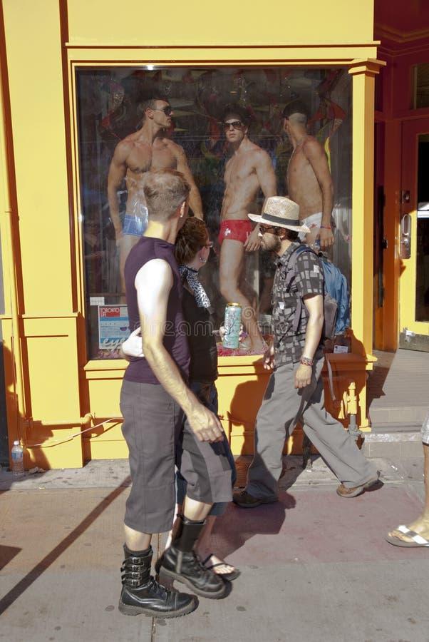 Leute betrachten männliche Baumuster in einem Systemfenster stockfotografie