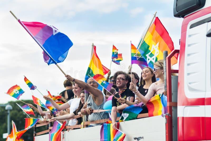 Leute in den wellenartig bewegenden Regenbogenflaggen des LKWs mit jüdischem Stern während Stockholms Pride Parade lizenzfreie stockfotografie