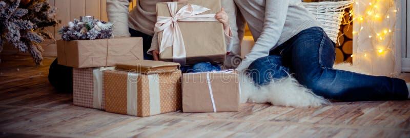 Leute der dreiköpfigen Familie, die Mutter, Vati und Tochter, sitzend auf dem Boden, um die Geschenke, das Mädchen halten einen e stockbild